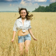 Running girl on wheat field — Stock Photo