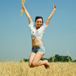 Jumping girl with wheat ear — Stock Photo