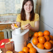 Woman adding orange to juicer — Stock Photo