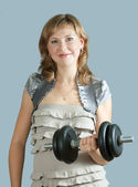 Woman in dress exercising with barbell — Stok fotoğraf