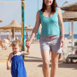 Mother with toddler walking on sand beach — Stock Photo