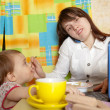 Businesswoman feeding baby and  speak by mobile — Стоковая фотография