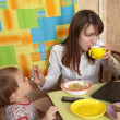 Mother and child eating breakfast - Stock Photo