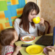 Stock Photo: Mother feeding baby and using latop