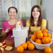 Women making fresh orange juice — Stock Photo #10520363