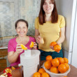 Women making fresh orange juice — Stock Photo