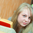 Girl reading book on sofa — Stockfoto
