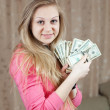 Stock Photo: Happy girl with bundles of US dollars