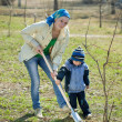 Stock Photo: Womwith her son resetting tree