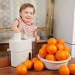 Baby girl making fresh orange juice — Stock Photo #10529824