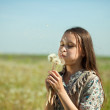 Stock Photo: Teenager girl blowing dandelion