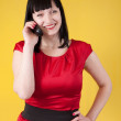 Stock Photo: Woman in red speak by phone over yellow