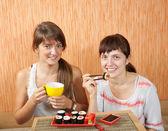 Dvě ženy jíst sushi rohlíky — Stock fotografie