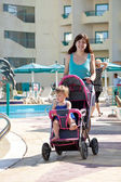 Mother with pram walking at resort — Stock Photo