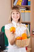 Businesswoman with basket of orange — Stock Photo