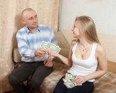 Wife gives her husband the money — Stock Photo