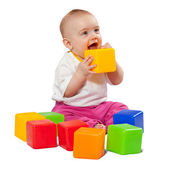 Happy baby plays with toy blocks — Stock Photo