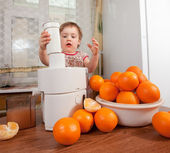 Baby girl making fresh orange juice — Stock Photo