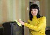 Donna spazza la polvere in tv — Foto Stock