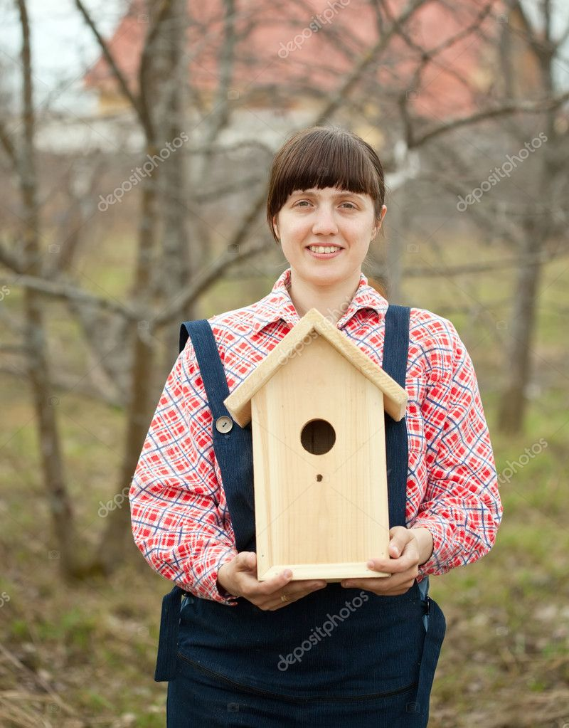 Woman with new birdhouse at garden  Stock Photo #10520001