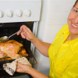 Royalty-Free Stock Photo: Woman cooking  chicken in oven