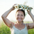 Stock Photo: Mature womin camomile chaplet