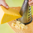 Closeup of cook grating cheese - Stock Photo