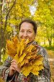 Senior woman with maple leaves — Stock Photo