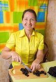Woman slicing prune — Stock Photo