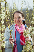 Happy mature woman against spring — Stock Photo