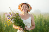 Mature woman with flowers posy — Stock Photo