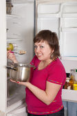 Woman eating from pan near fridge — Stock Photo