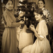 Vintage photo of daughters with mother decorating Christmas tre — Stock Photo #8090636