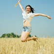 Jumping girl in field — Stock Photo