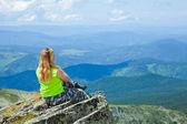 Kvinna sitter på bergstopp — Stockfoto