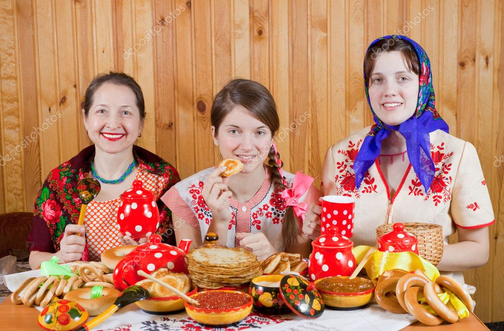 Women in traditional  clothes eating pancake with tea during  Shrovetide — Stock Photo #8090641