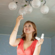 Girl changes light bulb - Lizenzfreies Foto