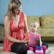 Mother and baby plays with pyramidion — Stockfoto #8138998