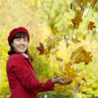 Woman throwing  maple  in autumn - Stock Photo