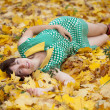 Girl lies in maple leaves — Stock Photo