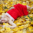 Foto de Stock  : Girl lies in maple leaves