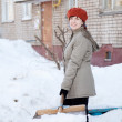 Girl throwing snow with shovel — Stock Photo