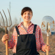 Happy farmer with spade and pitchfork — Stock Photo #8139313
