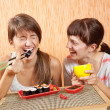 Foto Stock: Happy women eating sushi rolls
