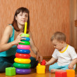 Mother and baby plays with pyramidion — Stockfoto #8139527