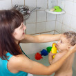Mother wasing  baby in bath - Stock Photo