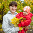 Happy mother with baby in autumn — Stock Photo