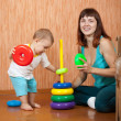 Foto Stock: Mother plays with baby