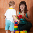 Happy mother and baby plays with toys — Stock Photo
