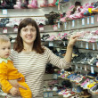 Happy mother with child chooses baby shoes — Foto Stock